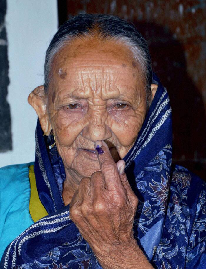 An elderly woman shows her inked finger after casting her vote for Lok Sabha polls, at a polling station in Dehradun on Wednesday. (PTI)