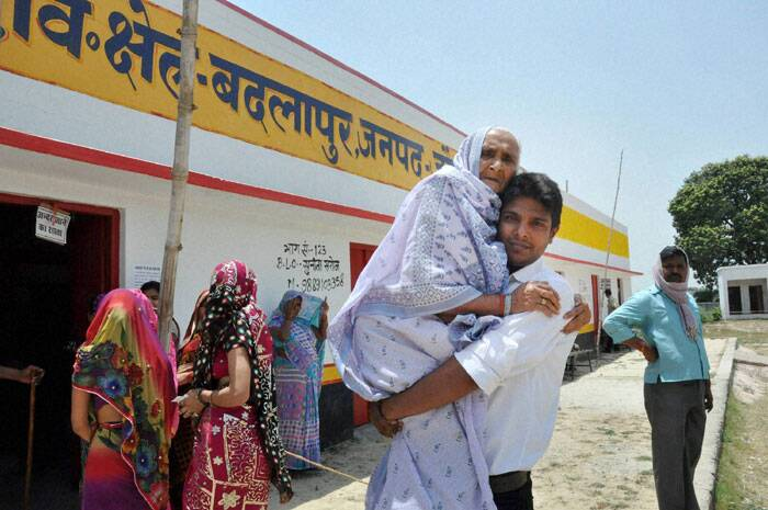 An old woman is carried to a polling booth to cast her vote for the last phase of Lok Sabha polls in Jaunpur on Monday. (PTI)