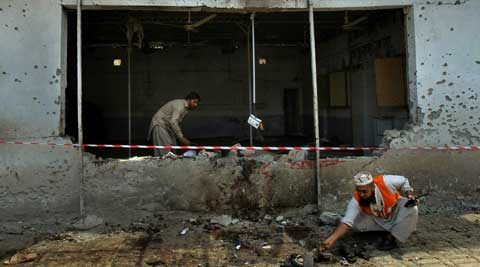 Pakistani investigators collect evidence at the site of a deadly bomb explosion on a soccer field in northwestern city of Peshawar, Pakistan, Sunday, May 11, 2014. (AP)