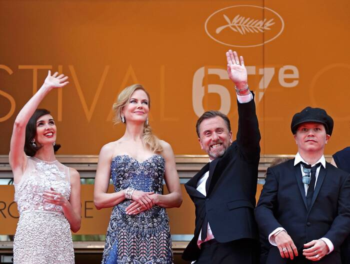Actress Paz Vega, who plays Maria Callas in the film, waves to the crowd with Tim Roth while Nicole Kidman smiles as they stand at the top of the stairs on their arrival at the 67th Cannes Film Festival and the screening of the 'Grace of Monaco'. (Source: AP)