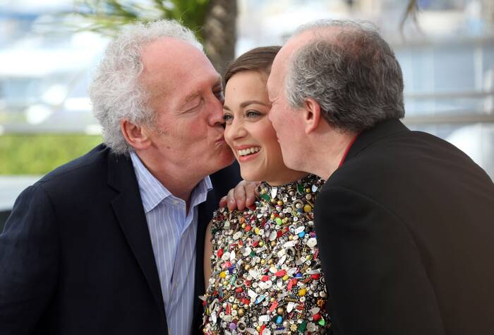 Marion Cotillard gets kisses from her directors Jean-Pierre Dardenne and Luc Dardenne. (Source: AP)