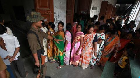 CRPF personnel instructs women voters to stand in a queue in Berhampore polling booth. ( Source: Express photo by Subham Dutta )