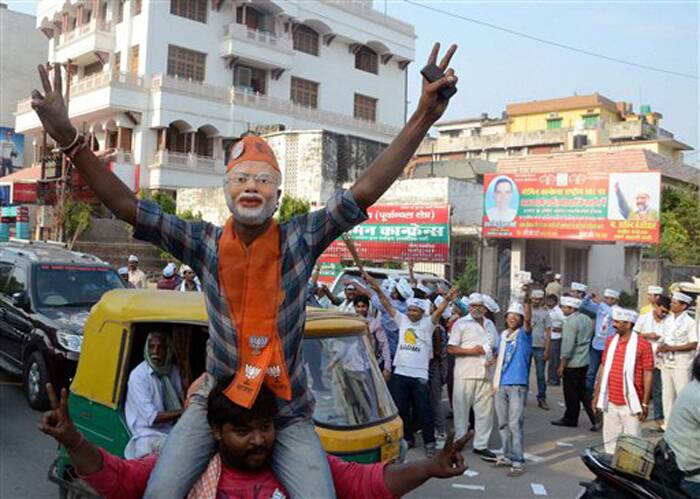 A BJP supporter, dressed up like Narendra Modi, flashes victory sign as AAP supporters look on at Sigra in Varanasi. (PTI)
