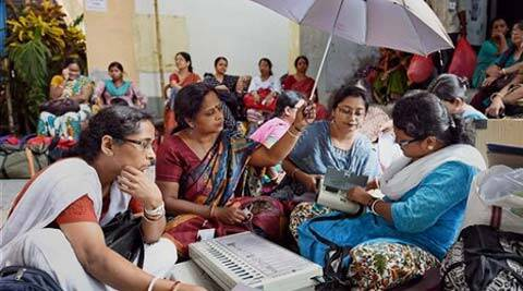 Women Polling officials busy checking EVM at an EVM distribution centre on the eve of last phase of elections. (Source: PTI)