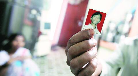 Father of Santosh Shelar (20), who is suspected to have joined Maoists, shows his photograph. (Express photo by Arul Horizon)