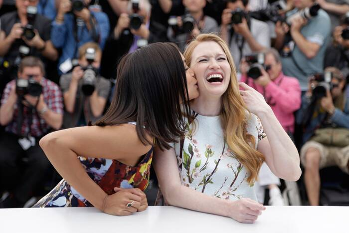 Rosario Dawson gives her giggling co-star Mireille Enos a peck on the cheek, while the paps clicked away. (Source: AP)