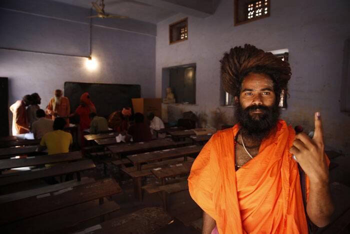 A sadhu displays the indelible ink mark on his finger after casting his vote during the eighth phase of voting in Haridwar. (AP)