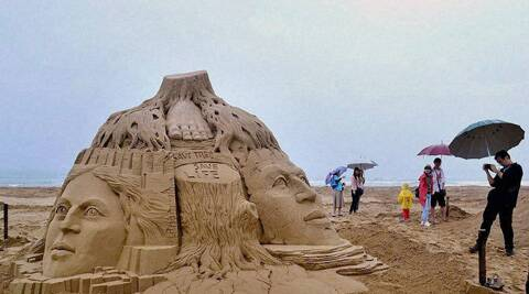 "Visitors look at a sand sculpture created by Sudarsan Pattnaik with a message ""Save Tree, Save Life"" at the Taipei International Sand Sculpture Championship 2014  at Fulong beach in New Taipei City in Taiwan."