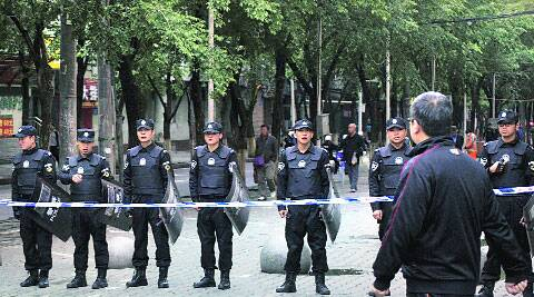 Policemen stand guard near the site of Thursday's blast in Urumqi Friday. ( Source: AP )