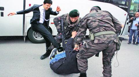 A protester is kicked by Yusuf Yerkel (L), adviser to Turkey's PM Tayyip Erdogan, as Special Forces police officers detain him in Manisa province on Thursday. ( Source: Reuters )