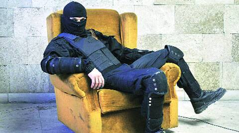 A masked pro-Russian protester poses for a picture inside a regional government building in Donetsk.