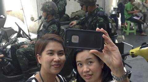 Residents stop to take a photograph of themselves at a military checkpoint in central Bangkok, Thailand. (AP)