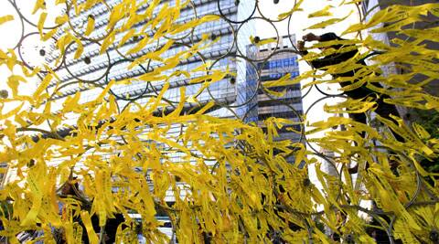 A man ties a yellow ribbon after paying tribute to the victims of the sunken ferry Sewol as yellow ribbons are displayed as a sign of hope for the safe return of missing passengers at a group memorial altar in Seoul. (AP)