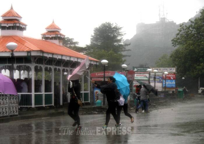 Girls battle with an umbrella during strong winds and rainfall in Shimla. ( Source: Express photo by Lalit Kumar)