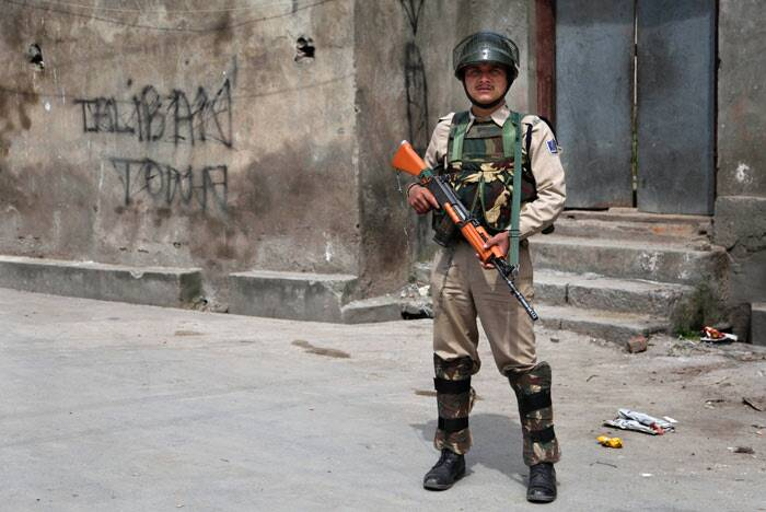 A paramilitary soldier stands guard on a street during curfew in Srinagar. <br /> The spokesperson said though there is no curfew in other areas where it was in force yesterday, but restrictions under section 144 have been imposed and security forces have been deployed in strength in such areas in view of the apprehensions of the law and order problems. (AP)