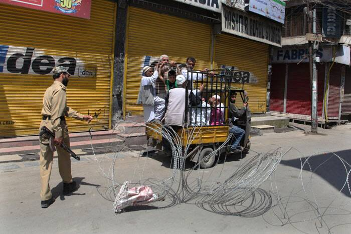 A policeman puts back in place a barbwire roadblock after allowing a vehicle carrying Kashmiris past during curfew in Srinagar. <br /> A youth, Bashir Ahmad Bhat, was killed on Wednesday when security forces allegedly opened fire to chase away stone-pelting protesters. (AP)