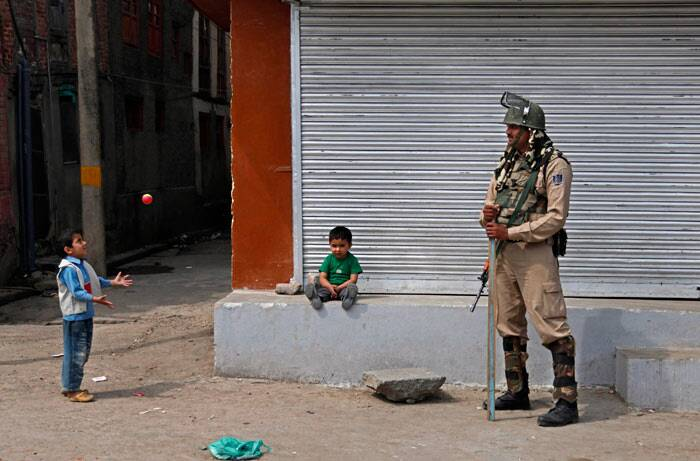 Children play near a paramilitary soldier standing guard at a closed market area during curfew in Srinagar. <br /> Curfew continued to remain in force in parts of the summer capital of Jammu and Kashmir on Friday as a precautionary measure but rest of the Valley observed a shutdown in wake of the killing of a youth when security forces allegedly opened fire on Wednesday. (AP)