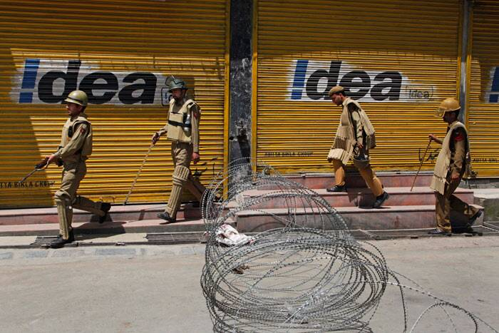 "Policemen patrol past a barbwire roadblock during curfew in Srinagar. <br />  ""Curfew will continue in five police station areas of Khanyar, Nowhatta, Rainawari, M R Gunj and Safakadal in the interior Srinagar city,"" a spokesman of the district administration said. (AP)"