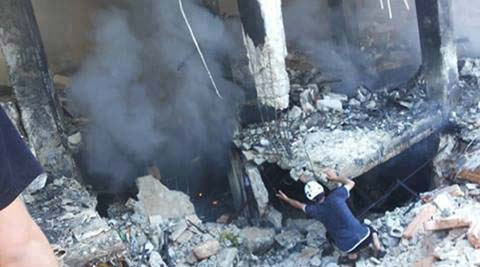 This photo provided by an anti-Bashar Assad activist group Edlib News Network (ENN), which has been authenticated based on its contents and other AP reporting, shows a Syrian man checking a damaged building at the scene where a car bomb exploded outside a mosque at Binnish town, in Idlib province, northern Syria. (AP)