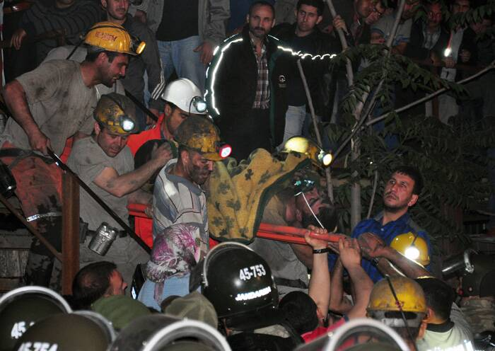 Rescuers struggled to reach more than 200 miners trapped underground early Wednesday after an explosion and fire at a coal mine in western Turkey killed at least 201 workers, authorities said, in one of the worst mining disasters in Turkish history.<br />Miners carry a rescued friend after an explosion and fire at a coal mine. (Source: AP)