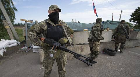 Pro-Russian armed militants guard a checkpoint blocking the major highway which links Kharkiv, outside Slovyansk, Ukraine. (AP)