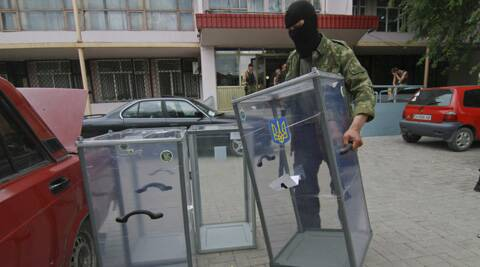 A Pro-Russian activist carries a ballot box away from a polling station preparing to smash it, in Donetsk, Ukraine. (AP)