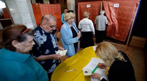 People wait in line at a polling station in the center of Slovyansk, eastern Ukraine, Sunday, May 11, 2014. Residents of two restive regions in eastern Ukraine engulfed by a pro-Russian insurgency are casting ballots