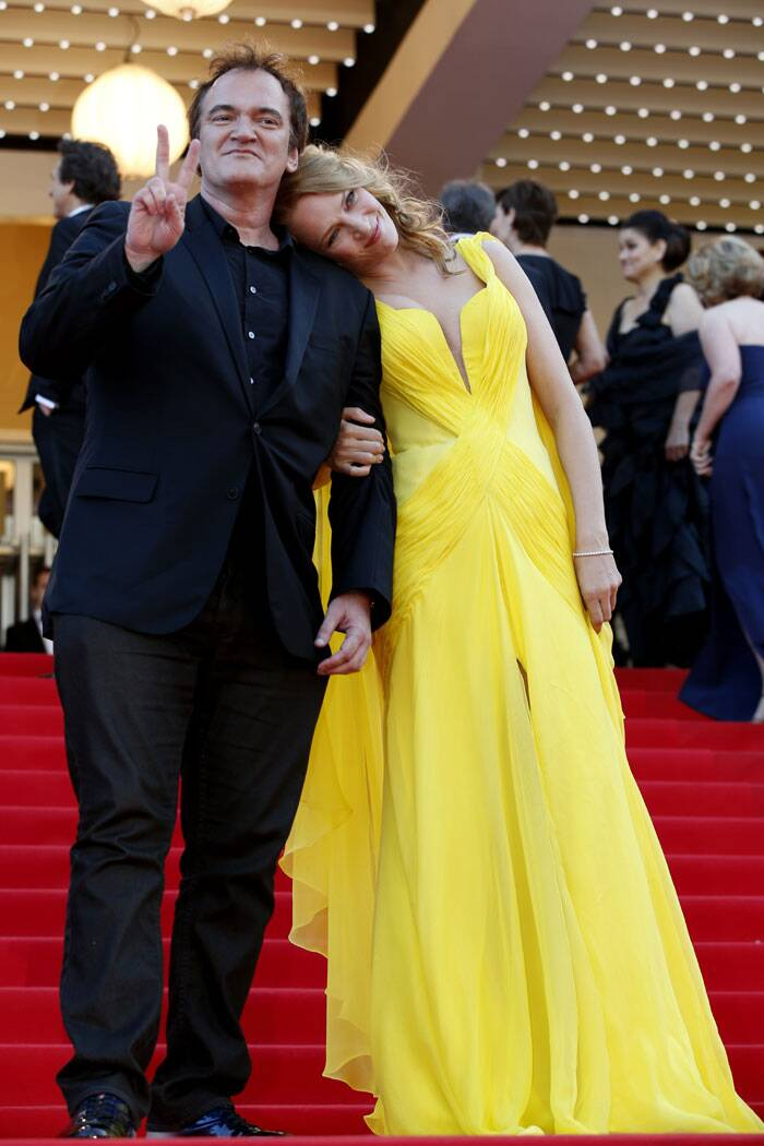 The actress cozies up to her 'Pulp Fiction' director Quentin Tarantino as they pose for pictures. (Source: AP)