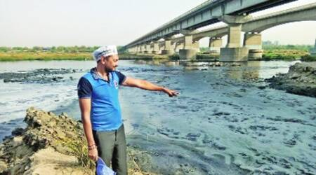 An AAP worker points out at 'polluted' Sabarmati water at Gyaspur near Ahmedabad Wednesday. Express