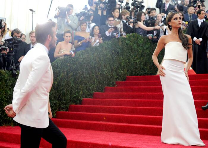 David Beckham waits patiently as his wife Victoria enjoys the spotlight for a bit. (AP)