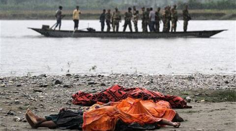 Bodies of victims killed in violence lie covered in the rain on the banks of the River Beki, as security officers patrol the area on a boat at Khagrabari village, in Assam on Saturday. (AP)