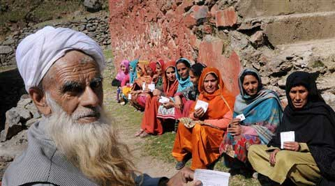 An elderly man and a group of women show their voter cards as they wait to cast their votes at a polling booth in Ganderbal. (File photo: PTI)