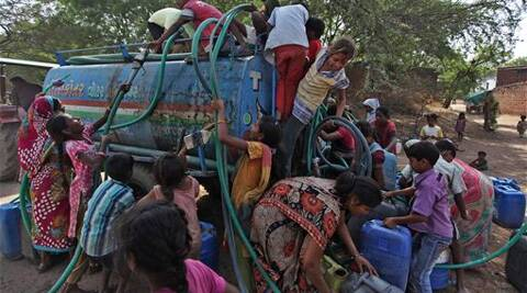 Women and children struggle to collect government-supplied water from a mobile tanker. (Source: AP)