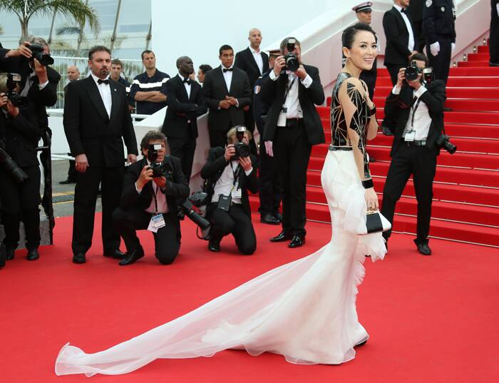 Chinese actress Zhang Ziyi went glam in a Rolland Haute Couture dress with Brian Atwood shoes, Bochic clutch, and Chopard jewelry. Seen here, the actress shows off her long train as she arrived for the 67th Cannes Film Festival and the screening of the 'Grace of Monaco'. (Source: AP)