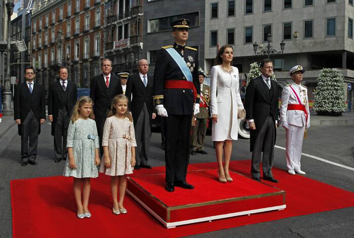 Spain's new king, Felipe VI, was sworn in on Thursday in a low-key ceremony which monarchists hope will usher in a new era of popularity for the troubled royal household.<br /><br />Spain's newly crowned King Felipe VI listens to the national anthem next to his wife Spain's Queen Letizia, their daughters Spain's Princess Leonor and Spain's Infant Sofia, left, and Spain's Prime Minister Mariano Rajoy, second right, outside the Spanish parliament, in Madrid. (Source: AP)
