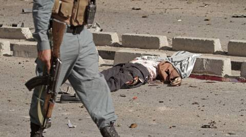 An Afghan police officer walks past the body of a civilian lying on the ground at the site of a suicide car bombing in Kabul, Afghanistan. (Source: AP)