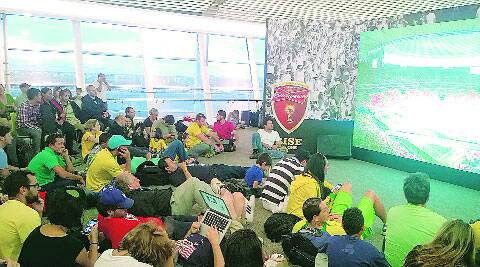 Fans stranded in the Brasilia airport watch the Brazil vs Cameroon game at the airport's mini fan-zone. ( Source: Express photo by Aditya Iyer )