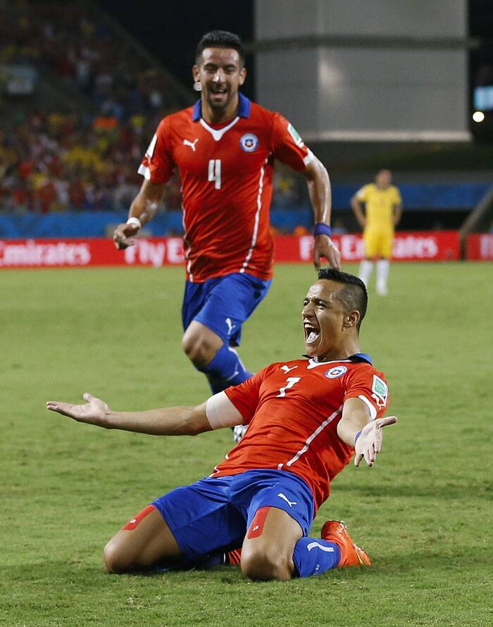 How about that: Chile's Alexis Sanchez slides with his hands spread out after scoring against Australia. (Source: AP)