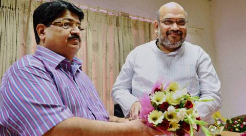 Newly elected president of the Gujarat Cricket Association, Amit Shah is greeted with a bouquet by Rajya Sabha MP Parimal Nathwani at the Motera Stadium in Ahmedabad on Friday. (Source: PTI)