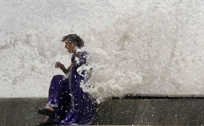 A eunuch enjoys high tide waves on the Arabian Sea coast in Mumbai. <br /> According to local reports, the city would witness high tides measuring 4.5 meters (15 feet) till Wednesday. (Source: AP)