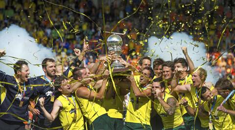 Australian players celebrate the World Cup after they defeated Netherlands 6-1 in the final. The successive men's World Cup title wins was a present the Australian team had promised to their coach Ric Charlesworth. (Source: AP)
