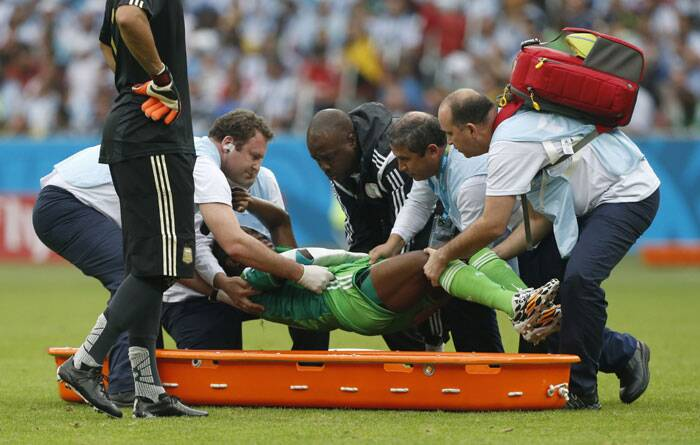 Nigeria's Michel Babatunde was ushered out of the pitch by medical staff due to an injury.  (Source: AP)
