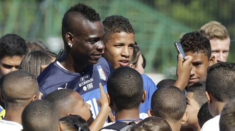 Italy striker Mario Balotelli interacts with fans during the practice session. Italy will have one foot in the second stage if they win. (Source: AP)