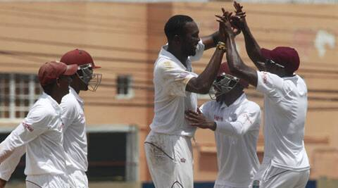 West Indies bowler Sulieman Benn, center, is congratulated by teammates after taking the wicket of New Zealand's batsman Jimmy Neesham. (Source: AP)