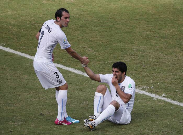 Uruguay captain Godin helps Suarez to get on his feet. Godin scored the lone goal of the match which gave Uruguay the win and a spot in last 16. (Source: Reuters)