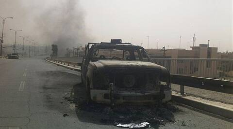 An Iraqi police vehicle is seen burned on a street of the northern city of Mosul, Iraq, on Thursday. (Source: AP)