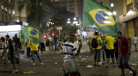 A fan holds up a Brazilian flag in the street after the Mexico vs. Brazil match (Source: AP)
