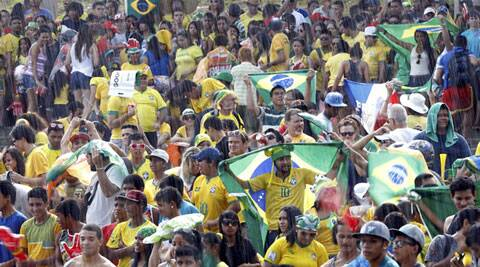 Brazil fans wait under the rain to watch a telecast of the 2014 World Cup Group A soccer match between Brazil and Mexico, at a fan fest in Manaus (Source: Reuters)