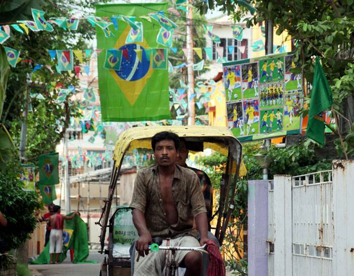 A rickshaw-puller passes through a lane decorated with Brazil's flags and photographs in South Kolkata. (Source: IE Photo by Partha Paul)