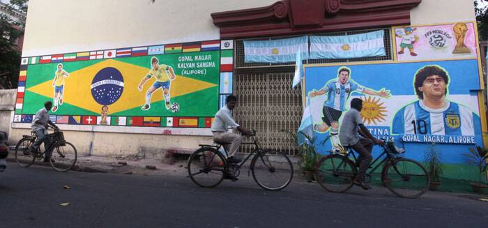 A wall in Gopal Nagar, Alipore, is adorned with paintings of Brazil's Neymar and Fred, and Argentina's Lionel Messi and former great Diego Maradona. (Source: IE Photo by Partha Paul)